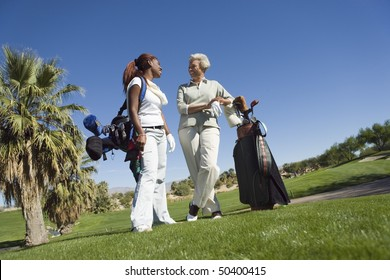 Grandmother and granddaughter on golf course, smiling