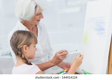 Grandmother and granddaughter painting together at home