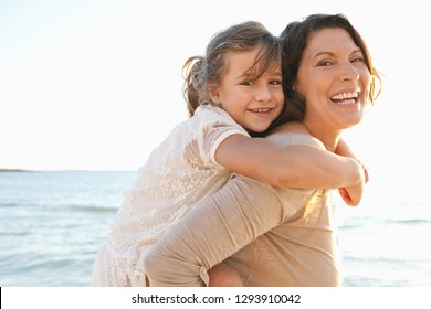 Grandmother and granddaughter playing on beach, carrying kid hugging, piggy back fun games, looking smiling outdoors. Family bonding together on summer holiday, travel activities recreation lifestyle.