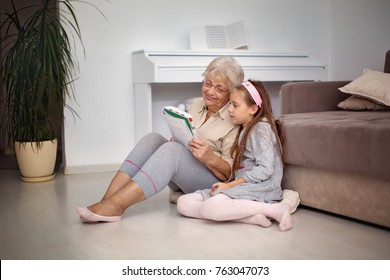 Grandmother with granddaughter reading a book.