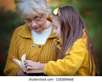 Grandmother with granddaughter reading book in autumn park