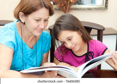 Grandmother and granddaughter reading a book at home