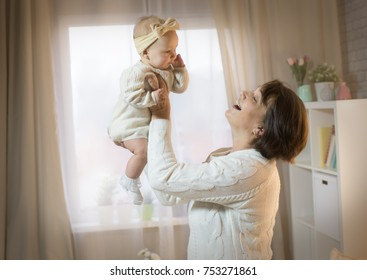 grandmother and granddaughter in the room, happy family with the baby