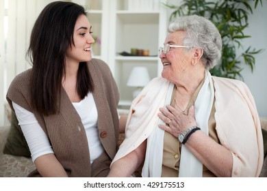 a64376d16ce Grandmother and granddaughter sitting on sofa and looking at each other