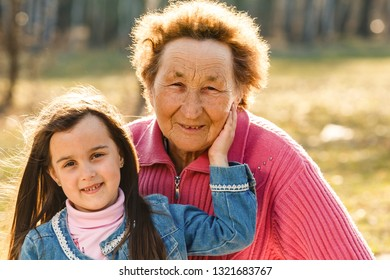 Grandmother And Granddaughter Sitting In Park Together