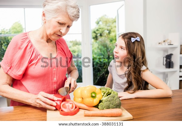 Grandmother and granddaughter slicing vegetables in the kitchen