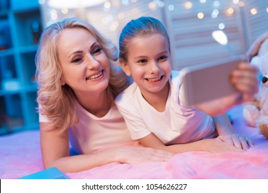 Grandmother and granddaughter are taking selfie on bed at night at home.