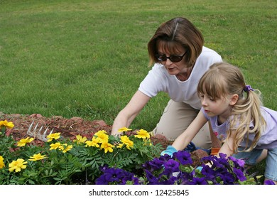 Grandmother and granddaughter tending a garden in a scenic field