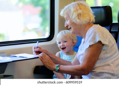 Grandmother with granddaughter traveling together by train. Cute tittle girl looking at the window and drawing sitting next to an elderly woman