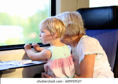 Grandmother with granddaughter traveling together by train. Cute tittle girl looking at the window sitting on woman's lap