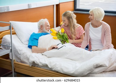 grandmother and granddaughter with tulip flowers visiting patient in hospital. male patient in hospital bed concept