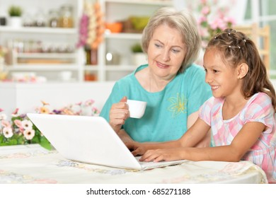 Grandmother with granddaughter use a computer