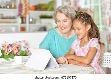 Grandmother with granddaughter use tablet