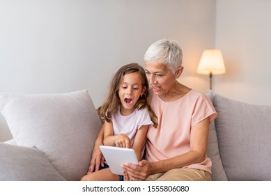 Grandmother and granddaughter using digital tablet on sofa in living room at home. Grandmother taking the common selfie with a child, using a tablet. Grandmother with granddaughter playing in a tablet