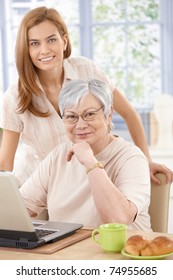 Grandmother and granddaughter using laptop at home, smiling, looking at camera.?
