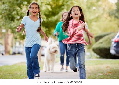 Grandmother And Granddaughters Walking Dog Along Suburban Street