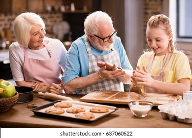 grandmother, grandfather and granddaughter cooking and kneading dough for cookies at kitchen table, cooking in kitchen concept