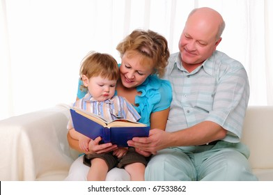 Grandmother, grandfather and grandson reading a book together. Symbol of the family.