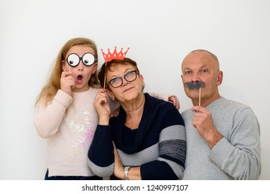 Grandmother and Grandfather with paper mask having fun with grandchild . Happy family celebrating new year, birthday , christmas, purim. Old funny grandpa with fake mustache, grandma with crown.