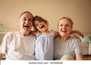 Grandmother and grandfather playing end enjoying with their granddaughter.