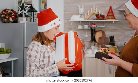 Grandmother with grandfather sharing xmas present gift with ribbon on it during christmastime in decorated home kitchen. Happy family celebrating christmas holiday enjoying winter season