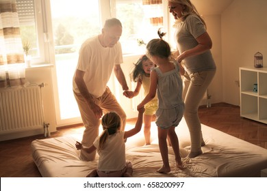 Grandmother and grandfather  together with their granddaughters dancing on the bed.