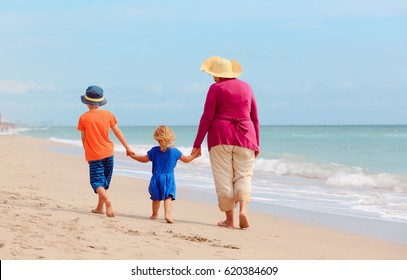 grandmother with grandkids- little boy and girl- walk at beach