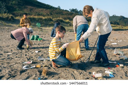 Grandmother and grandson with group of volunteers picking up trash on the beach