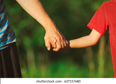 grandmother and grandson holding hands in nature