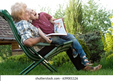 Grandmother and grandson reading a book outdoors.Funny stories.