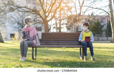 Großmutter und Enkelsohn durch soziale Distanzierung auf Parkbank getrennt
