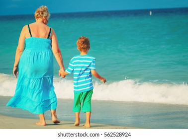 Grandmother and grandson walking at tropical beach