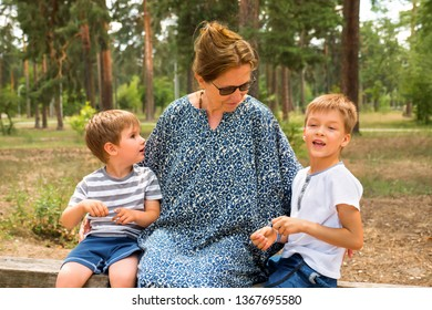 Grandmother with grandsons. Happy childhood concept. Multi-generation family. Preschool lifestyle. Smiling boys with happy nurse. Kids sitting in the park. Siblings playing. Brothers having fun