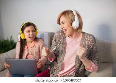 Grandmother with granndaughter smiling and listening to music with headphones.