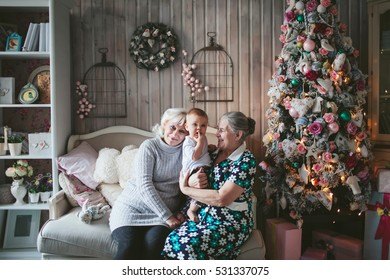 grandmother and great-grandmother with a baby in a Christmas tree