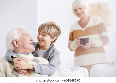 Grandmother and happy boy embracing his beloved grandfather