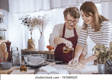 Grandmother helping her granddaughter make dough by adding olive oil