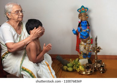 Grandmother helps a child to have the first sight of Lord Krishna as ritual practiced during 'Vishu' festival in Kerala, India.