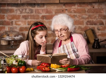 Grandmother and her cute granddaughter searching for a recipe in old cooking book