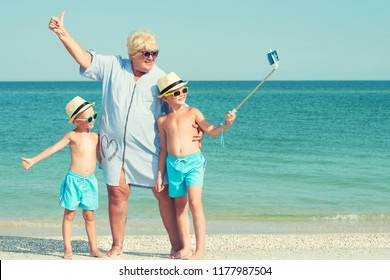 Grandmother with her grandchildren are resting on the sea, they are make a selfie on the beach.