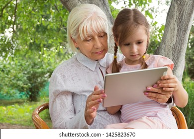 Grandmother with her granddaughter studying a book on a tablet, work on the tablet. Granny at the age of 70 years old with great granddaughter in her arms. Concept. Relationship in the family.