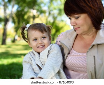 Grandmother with her little granddaghter in green summer park