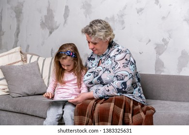 Grandmother and her little granddaughter are watching movies together and playing on the tablet while sitting on the sofa. Grandmom hugs granddaughter. Maternal care and love. Horizontal photo.