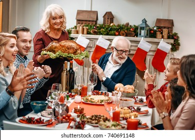grandmother holding christmas turkey while family clapping