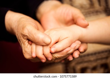 Grandmother holding the grand-daughter's hand, close-up photo. Family care, elderly and generation concept