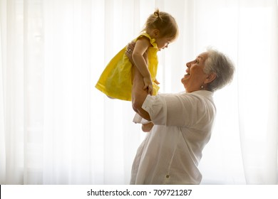 Grandmother holding little granddaughter in the room at home