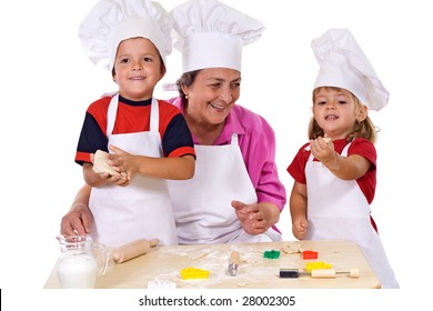 Grandmother with kids in chef hats making cookies, playing with the dough - isolated