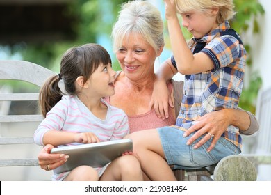Grandmother with kids playing games on tablet