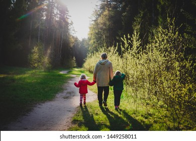 grandmother with kids walk in nature at sunset