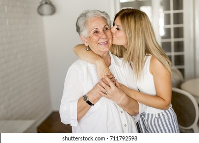 Grandmother kissing granddaughter in the room